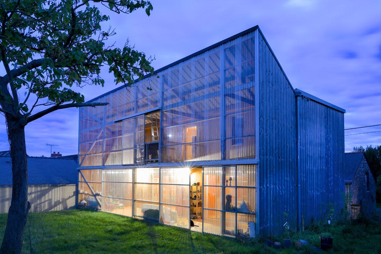 A_ Façade nord de la maison avec son jardin d'hiver derrière une paroi en polycarbonate